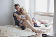 Portrait of young couple sitting on bed at home - FSIF01074