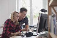 Young couple using computer against window at home - FSIF01080