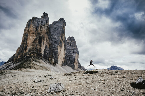 Low angle view of teenage boy jumping over rocks in alps against cloudy sky, South Tyrol, Italy - FSIF01083