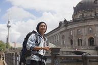Smiling young male tourist standing with map by railing against Bode Museum, Berlin, Germany - FSIF01089