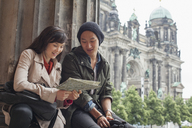 Low angle view of young friends reading map at Altes Museum against Berlin Cathedral, Germany - FSIF01098