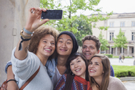 Smiling young woman taking selfie with multi-ethnic friends, Berlin, Germany - FSIF01101
