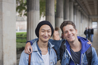 Portrait of smiling young male friends standing with arms around, Berlin, Germany - FSIF01104