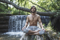 Shirtless man sitting with crossed legs on logs against waterfall at forest - FSIF01107