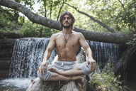 Full length of shirtless man sitting with crossed legs on logs against waterfall at forest - FSIF01110