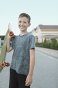 Portrait of smiling boy holding skateboard while standing on street - FSIF01125