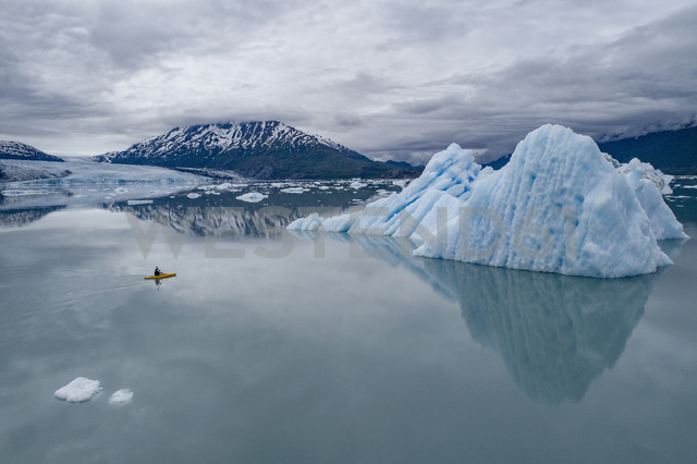 Person canoeing in lagoon by icebergs against cloudy sky, Lake George, Palmer, Alaska, USA - FSIF01128