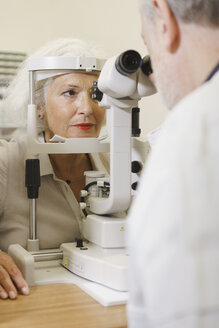 Doctor examining senior woman's eye at clinic - FSIF01134