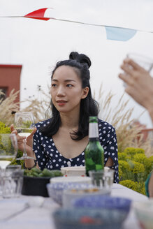 Thoughtful young woman holding wineglass while sitting at outdoor table during party - FSIF01176