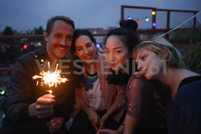 Portrait of happy man holding sparkler while sitting with female friends at night - FSIF01185