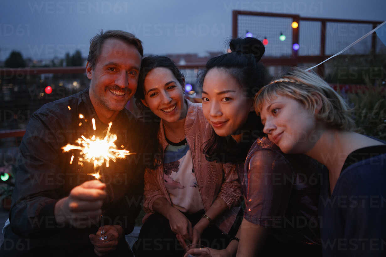 Portrait of happy man holding sparkler while sitting with female friends at night - FSIF01185 - fStop/Westend61