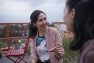 Happy woman talking to female friend while sitting on patio - FSIF01188