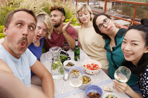 Portrait of playful friends making faces while sitting at outdoor table at patio - FSIF01191