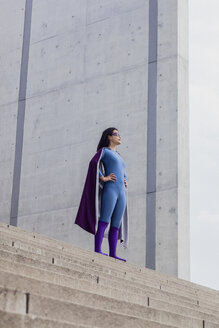 Low angle view of female superhero standing on steps against wall - FSIF01197