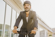 Low angle view of businessman cycling by building on sunny day - FSIF01200