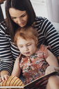 Mother reading book to daughter while sitting on sofa at home - FSIF01215