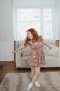 Happy girl with arms outstretched dancing on carpet at home - FSIF01218
