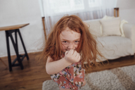 Portrait of happy girl dancing in living room at home - FSIF01227