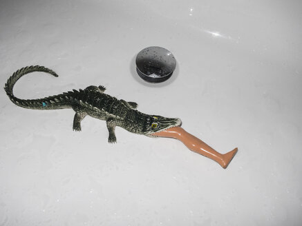 High angle view of crocodile toy eating plastic leg in white sink - FSIF01236