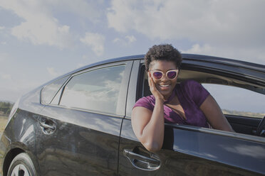 Smiling young woman sitting in car against sky - FSIF01248