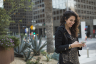 Smiling mid adult woman using mobile phone against buildings in city, Los Angeles, California, USA - FSIF01251