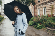 Portrait of teenage girl holding umbrella standing on street in town - FSIF01260
