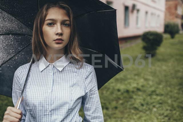 Portrait of teenage girl holding umbrella on grassy field - FSIF01263