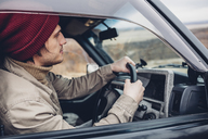 Side view of man wearing knit hat riding sport utility vehicle - FSIF01266