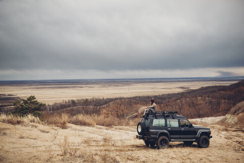 Distant man sitting on top of sports utility vehicle at field against cloudy sky, Amur, Russia - FSIF01269