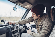 Man wearing knit hat and adjusting smart phone on dashboard of sports utility vehicle - FSIF01272