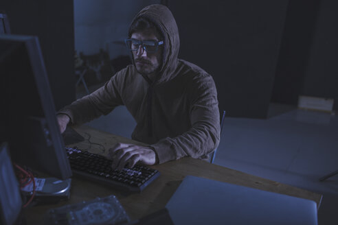 Serious computer hacker wearing hooded shirt using desktop computer at table in abandoned room - FSIF01284