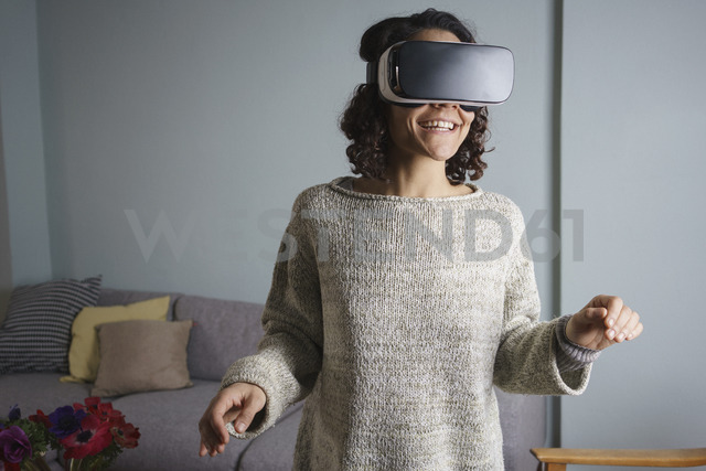 Happy woman using virtual reality headset while standing in living room - FSIF01327 - fStop/Westend61