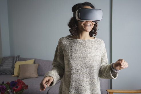 Happy woman using virtual reality headset while standing in living room - FSIF01327