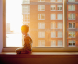 Side view of boy looking out while kneeling on window sill at home - FSIF01345