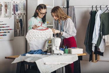 Trainee examining dress's fabric by designer holding coathanger at fashion studio - FSIF01348