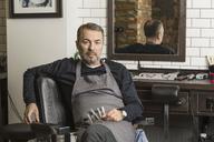 Portrait of mature barber sitting on chair at hair salon - FSIF01351
