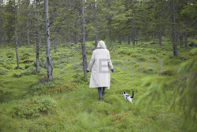 Rear view of woman wearing long coat while walking with cat on grassy field - FSIF01354 - fStop/Westend61