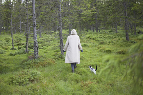 Rear view of woman wearing long coat while walking with cat on grassy field - FSIF01354