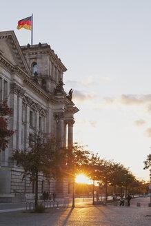 Germany, Berlin, Regierungsviertel, Reichstag building with German flag in autumn at sunset - GWF05433