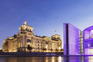 Germany, Berlin, Regierungsviertel, Reichstag building with German flags and Paul-Loebe-Building at Spree river in the evening - GWF05442