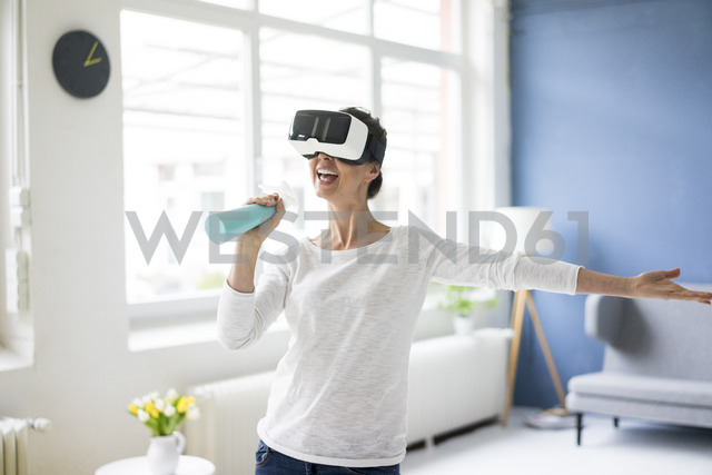 Vital woman at home cleaning wearing VR glasses - MOEF00802