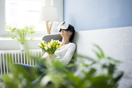 Smiling woman sitting on couch wearing VR glasses holding bunch of tulips - MOEF00805