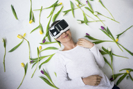 Smiling woman wearing VR glasses lying on floor amidst tulips - MOEF00811