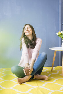 Smiling woman sitting on floor holding glass of juice - MOEF00814