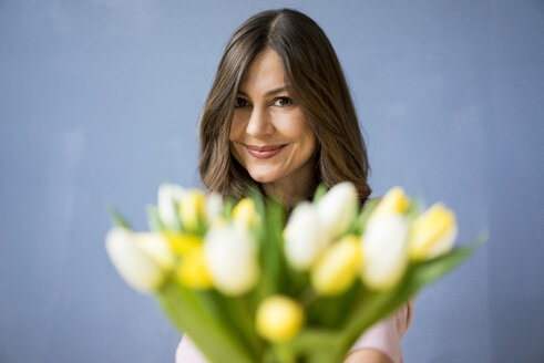 Portrait of smiling woman holding bunch of tulips - MOEF00817