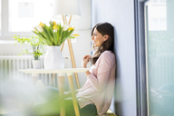Smiling woman sitting on floor next to table with tulips - MOEF00820