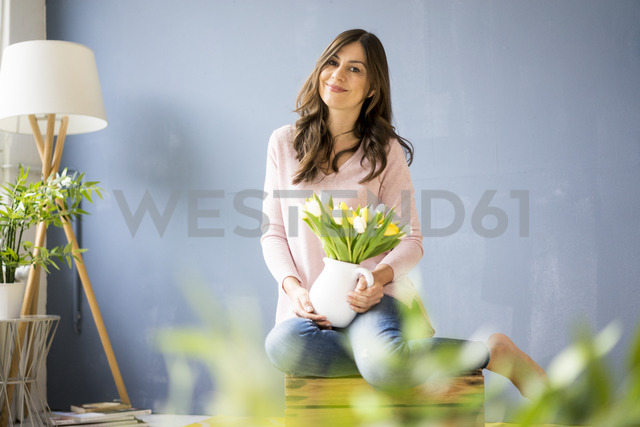 Portrait of smiling woman holding bunch of tulips in a jar - MOEF00829