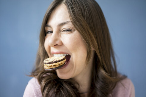 Portrait of happy woman eating a cake - MOEF00832