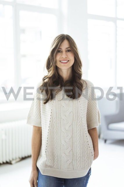 Portrait of smiling woman standing in bright room with window - MOEF00835