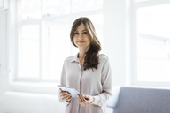 Portrait of smiling woman standing in bright room holding tablet - MOEF00841